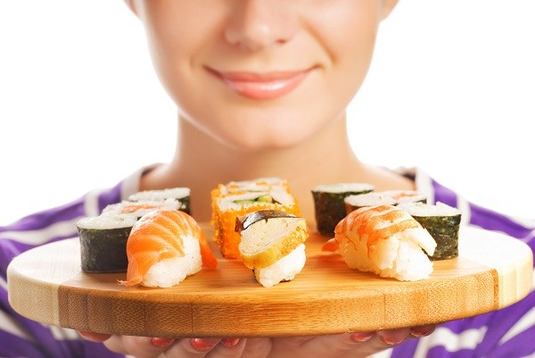 Happy woman holding bamboo plate with fresh sushi set on it (Sha