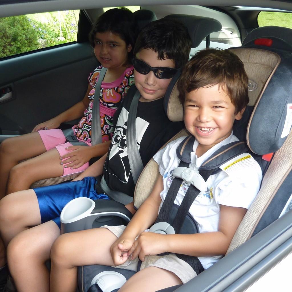 tre bambini in macchina con seggiolini