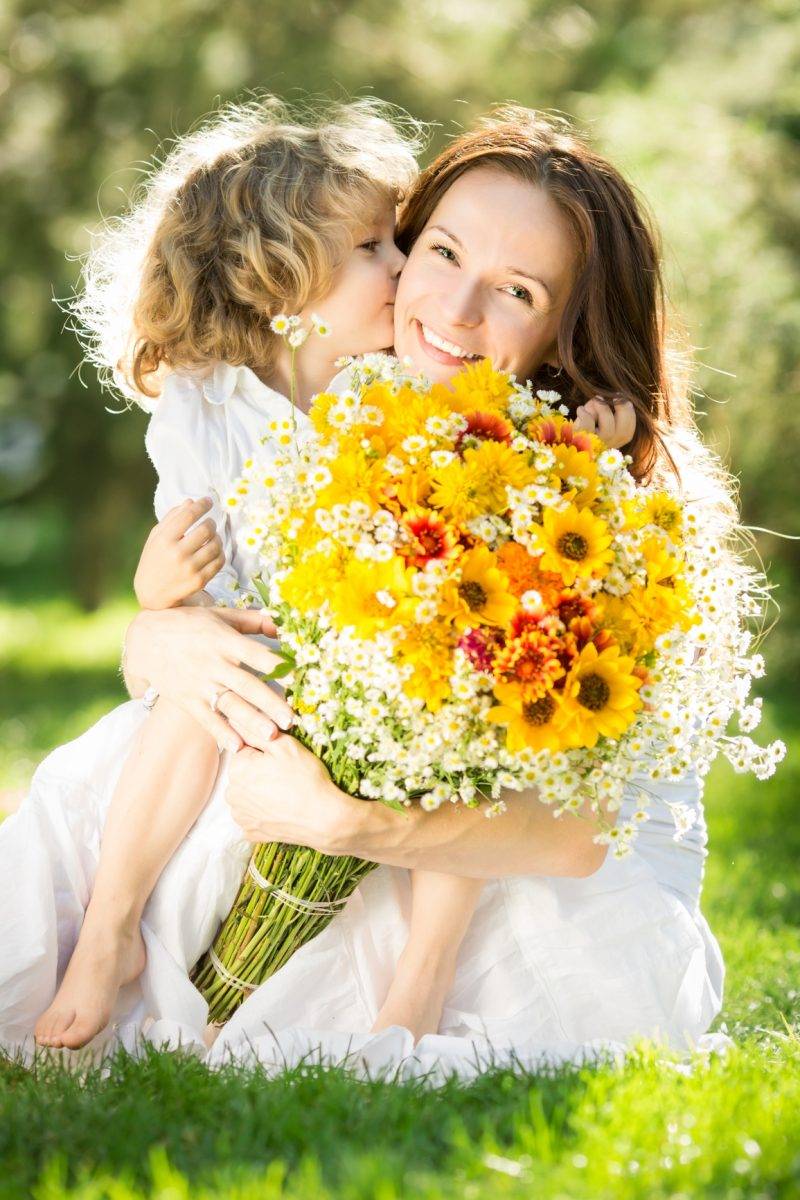bambina che regala fiori alla mamma