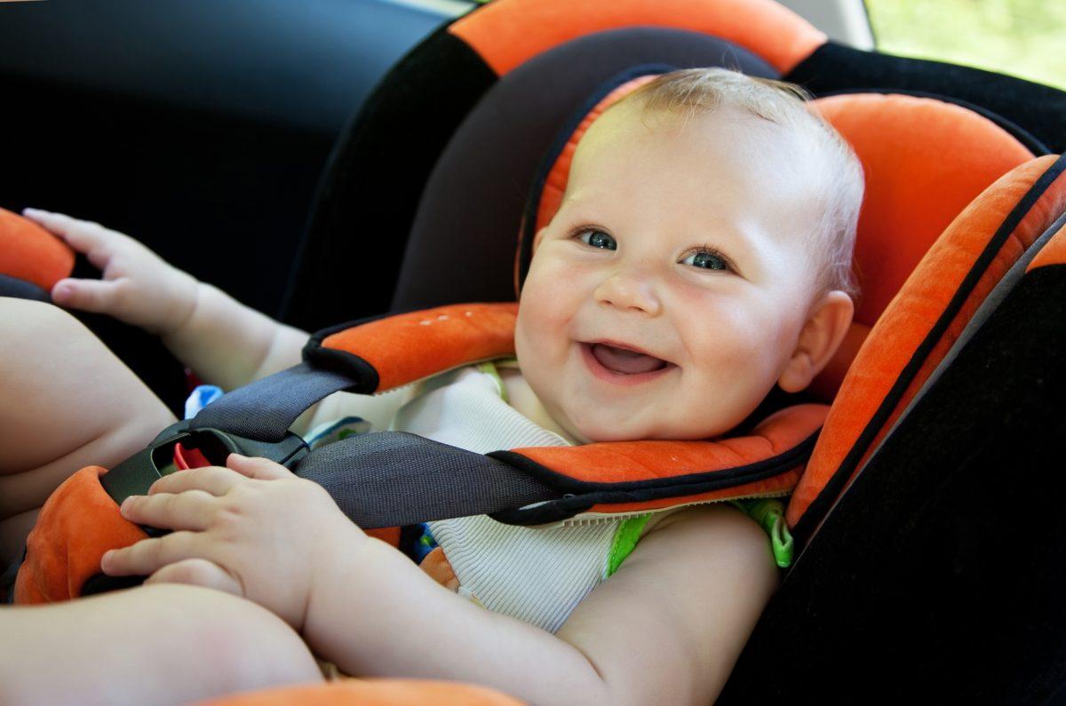 bambino sistemato nel seggiolino auto