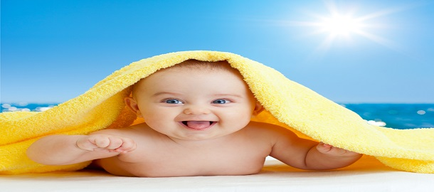 Adorable happy baby in colorful towel on sea beach