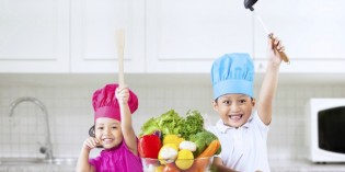 Two cheerful chef kids in kitchen