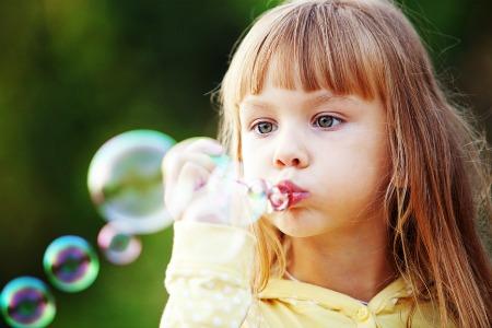 bambina che fa le bolle di sapone