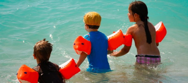 3 young children entering the sea with swimming bands on