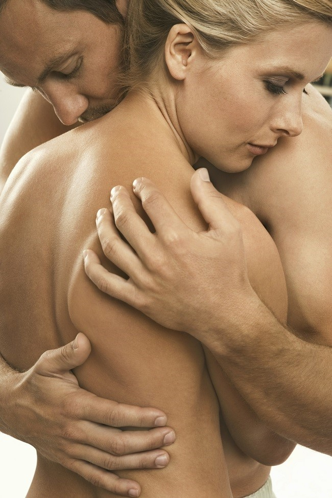 Close up of a naked couple hugging.