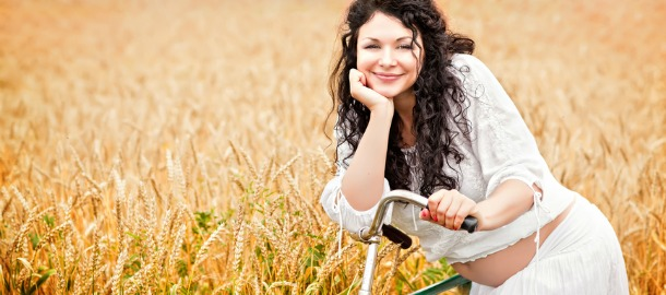 cute pregnant girl with a bicycle in a field