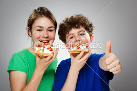 dep_9534435-Kids-eating-cake-with-cream-and-fruits