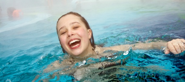 girl has fun in the outdoor thermal pool in wintertime