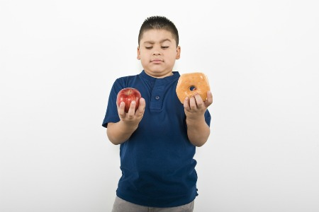 Young boy choosing between an apple and doughnut isolated over white background