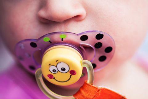 Bambino con ciuccio giallo