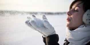 Donna che soffia la neve dalle mani