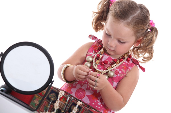 little girl with necklaces and mirror