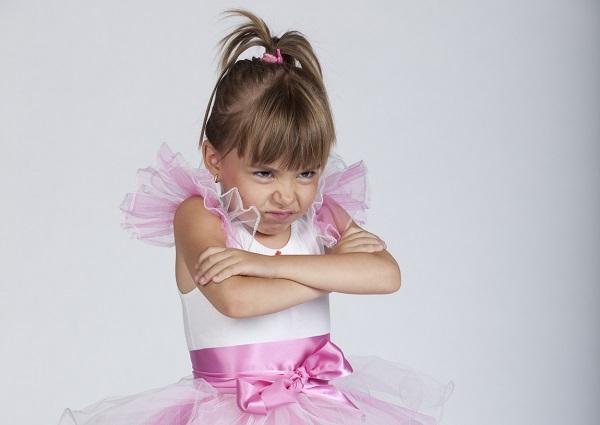 Little brat ballerina holding her arms crossed