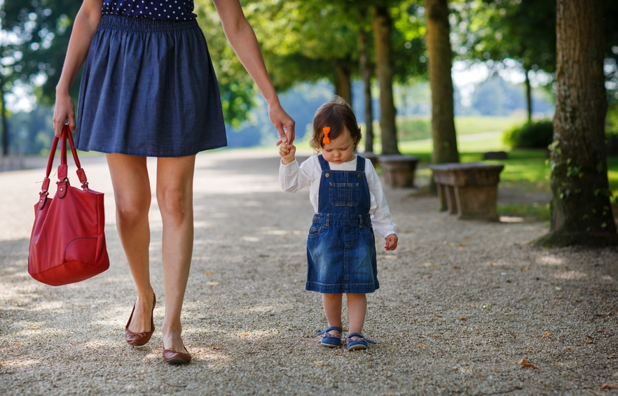 Little baby girl walking with beautiful mother in summer park