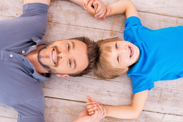 Happy dad and son. Top view of happy father and son holding hands smiling at camera while lying on the hardwood floor