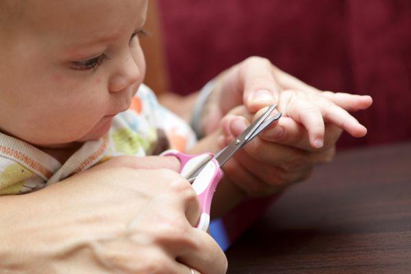 mamma intenta a tagliare le unghie al bebè