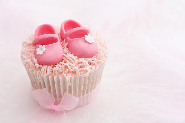 Cupcake decorato con scarpine neonato in pasta di zucchero