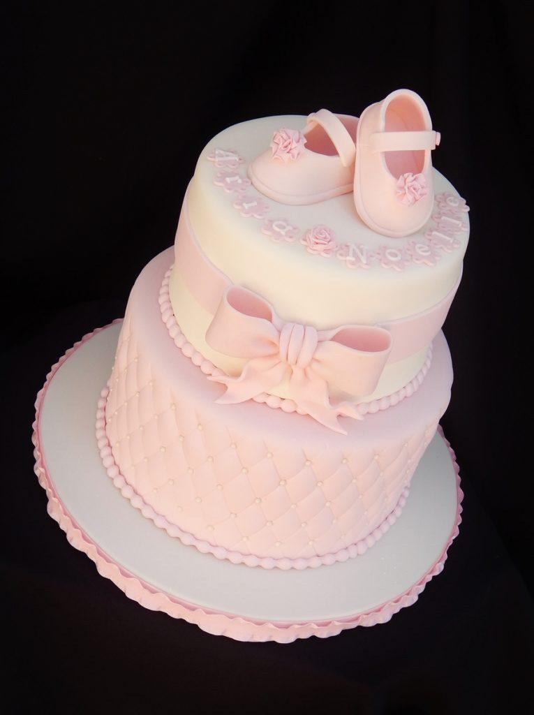 Torta battesimo con scarpine neonato in pasta di zucchero rosa con pon pon