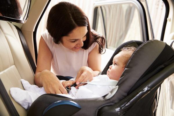Mamma mette il proprio bambino sul seggiolino contro il senso di marcia