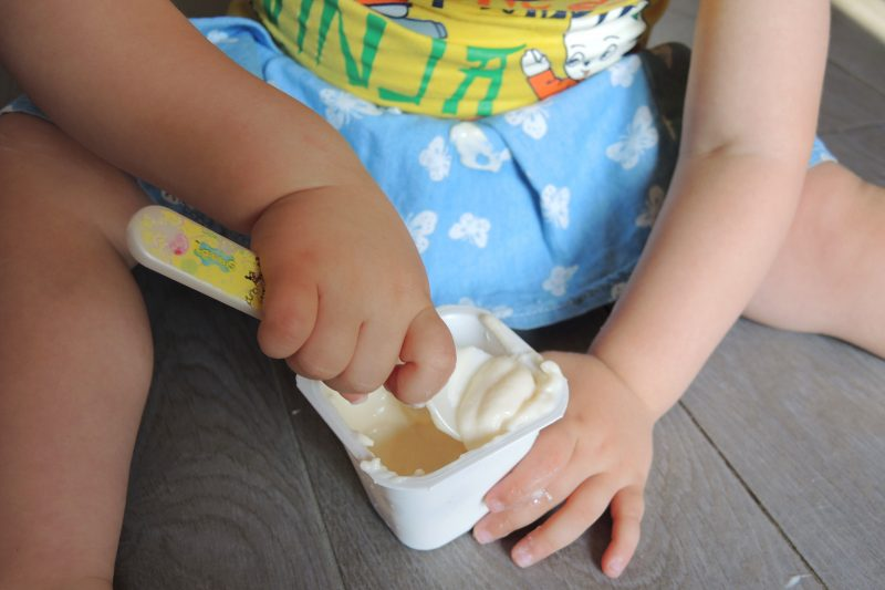 bambina che mangia merenda al latte Humana