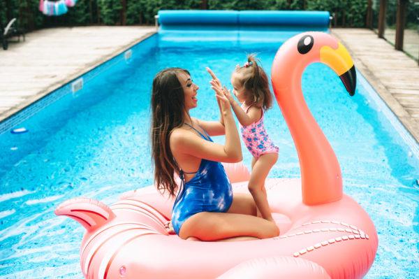 mamma e figlia su fenicottero rosa galleggiante