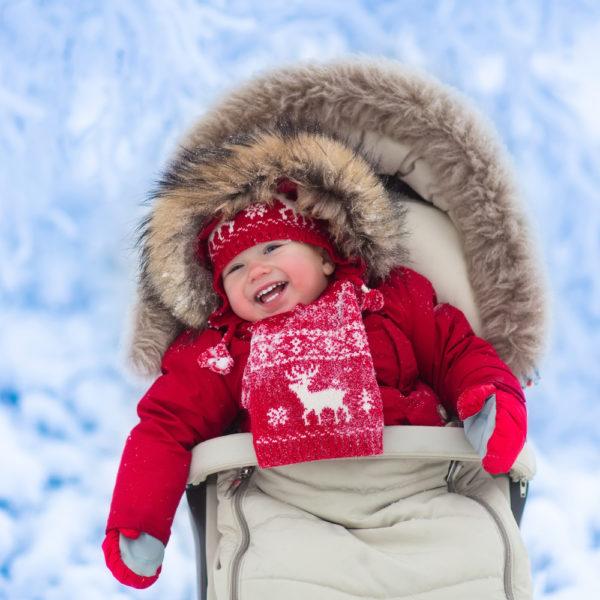 bambino sulla neve con passeggino