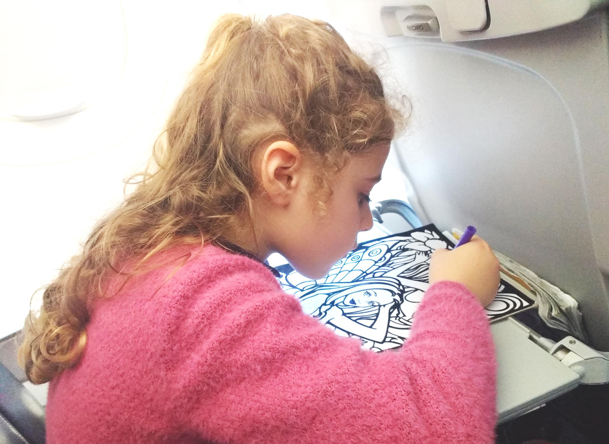 Viaggiare con i bambini- 5 consigli da tenere bene a mente_bambina in aereo