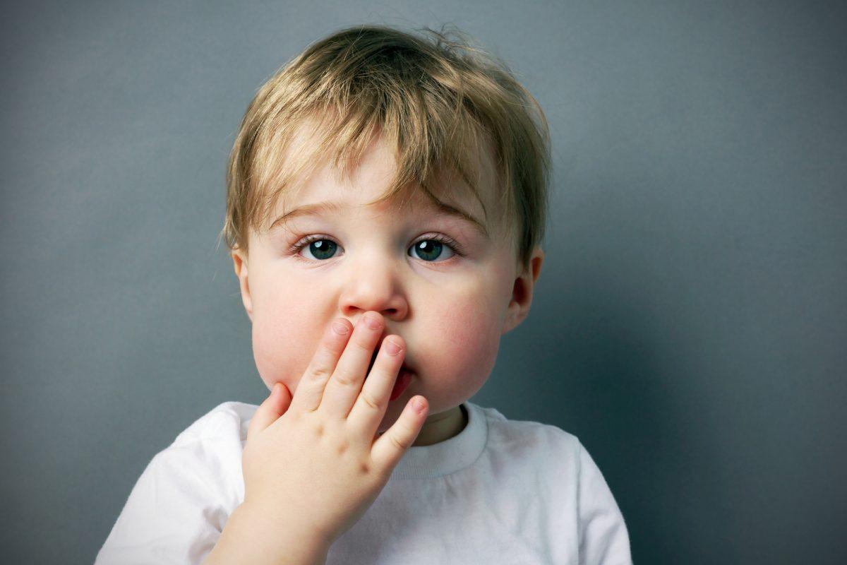bambino con mano sulla bocca