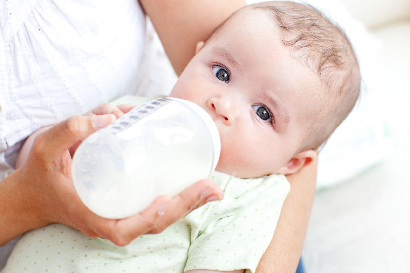 neonato che beve latte