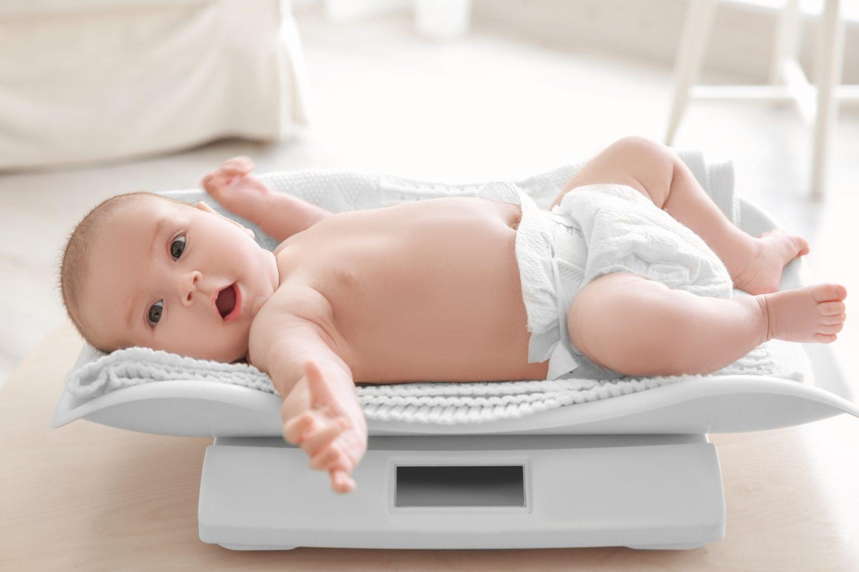 Bambino su bilancia per misurare tabella peso e altezza