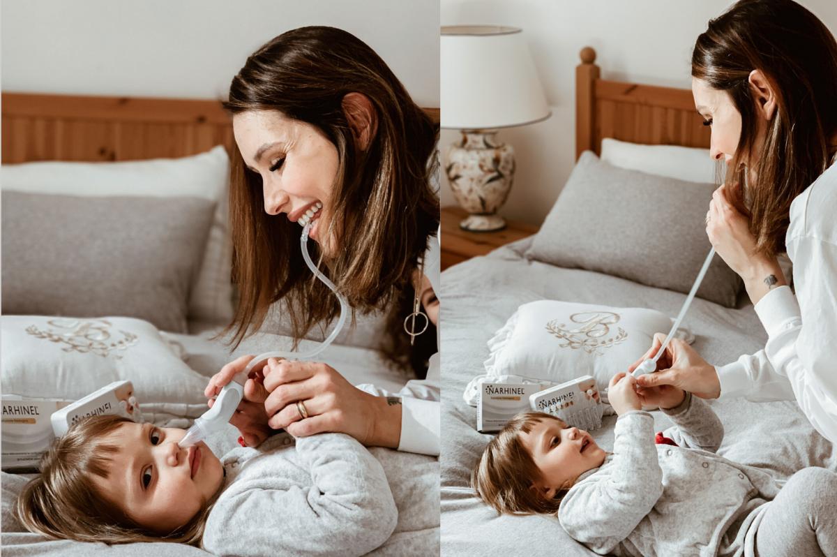 mamma che usa l'aspiratore nasale per pulire il naso dei bambini