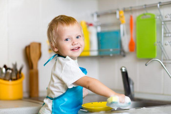 cosa fare la domenica con i bambini: bambino che lava i piatti