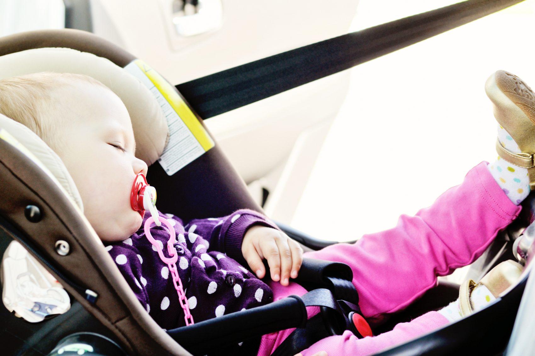 bambina che dorme su seggiolino auto