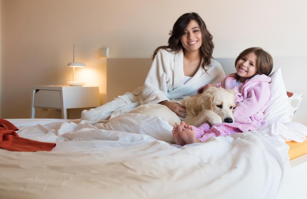 mamma e figlia con il cane sul letto