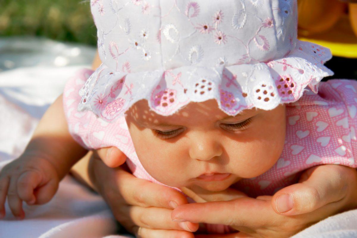 bambina con cappellino estivo per neonato