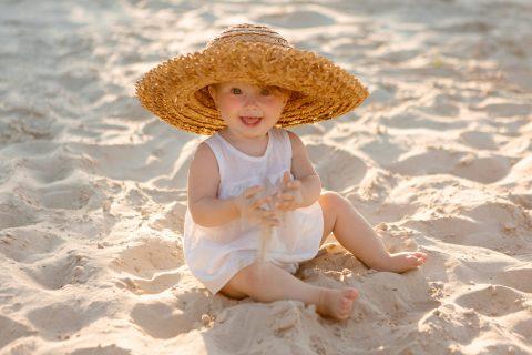 bambina sulla spiaggia all'ombra come progettere pelle dei bambin iin estate